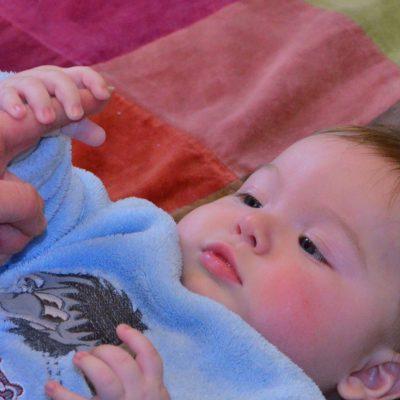 Baby erkundet einen Finger eines Erwachsenen