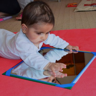 Baby spielt mit einem Spiegel
