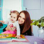 Junge Mutter schaut ein Bilderbuch mit ihrem Baby an
